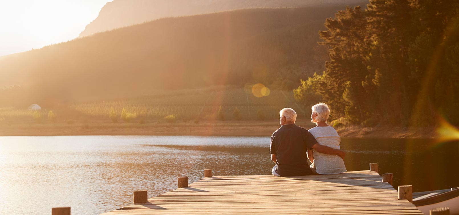 Retire couple sitting on a dock watching the sun set, Weller Capital
